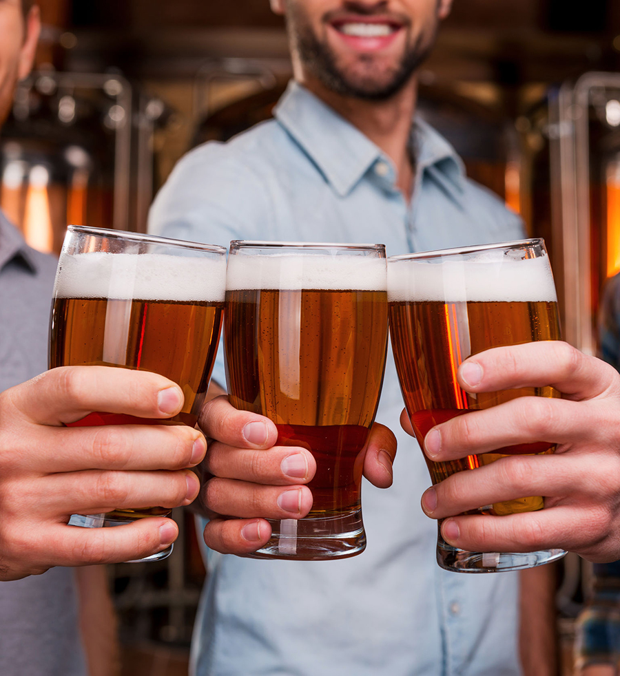 Cheers! Close-up of three cheerful young men in casual wear stretching out glasses with beer and smiling while standing in front of metal containers